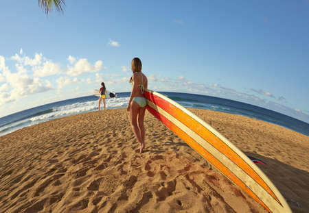 Women carrying surfboards on beach LANG_EVOIMAGES