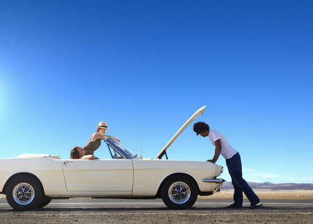 Friends stranded with broken down convertible on remote road LANG_EVOIMAGES