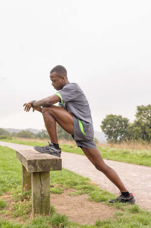 African American runner stretching on park bench LANG_EVOIMAGES