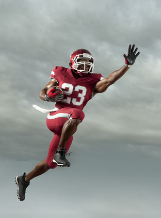 Black football player carrying football in mid-air