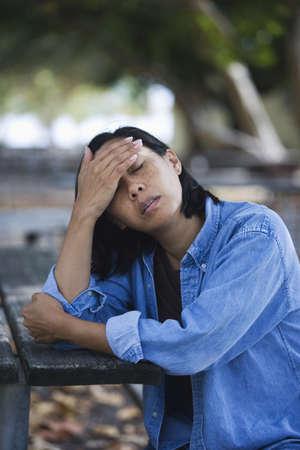 Worried Filipino woman sitting at picnic table