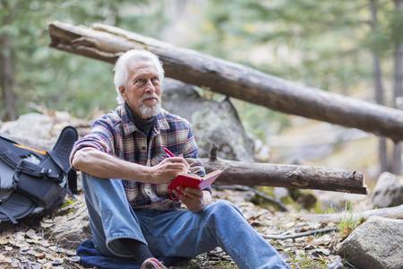 Caucasian hiker writing in forest LANG_EVOIMAGES