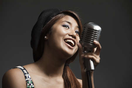 Filipino woman singing into microphone LANG_EVOIMAGES