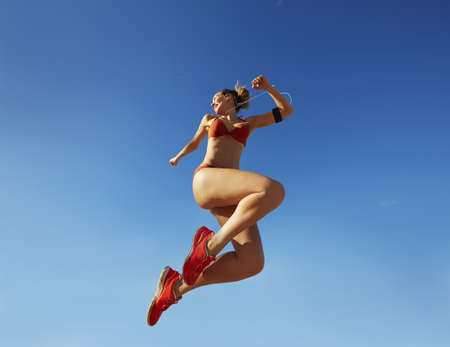 Pacific Islander woman jumping for joy under blue sky