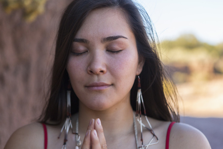 Mixed race woman praying in desert LANG_EVOIMAGES