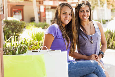 Friends sitting outdoors together with shopping bags LANG_EVOIMAGES