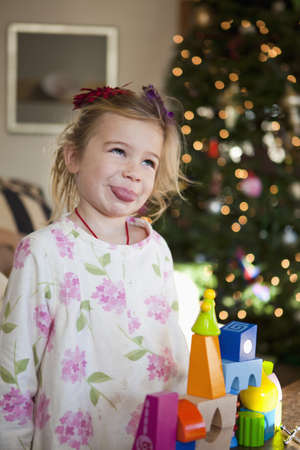 Caucasian girl sticking out tongue at Christmas LANG_EVOIMAGES