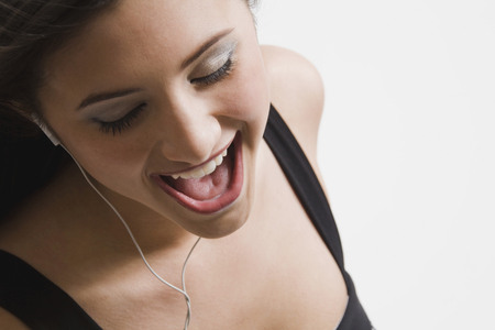 Mixed race woman listening to headphones and singing LANG_EVOIMAGES