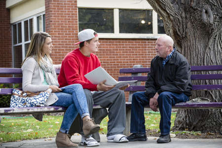 Students and teacher talking on park benches