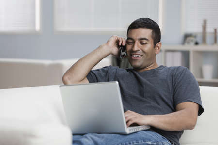 Hispanic man on sofa with laptop and talking on phone LANG_EVOIMAGES