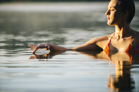 Caucasian woman swimming in still lake LANG_EVOIMAGES
