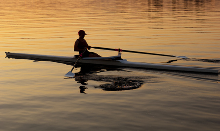 Person rowing sculling boat on river LANG_EVOIMAGES
