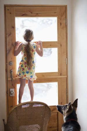 Caucasian girl peering out door window