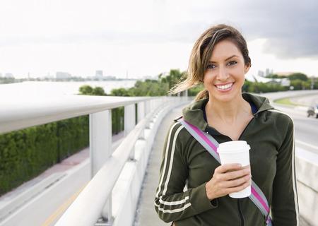 Hispanic woman walking outdoors with coffee