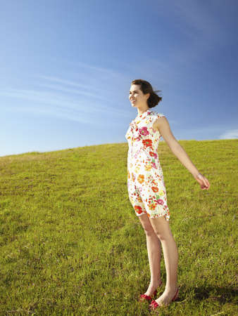 Caucasian teenager in dress standing in field LANG_EVOIMAGES