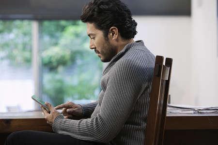 Hispanic man using digital tablet LANG_EVOIMAGES