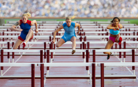Runners jumping hurdles in race LANG_EVOIMAGES