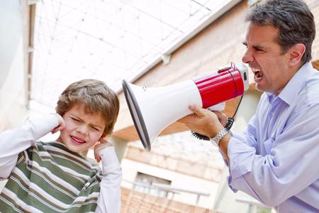 Hispanic father shouting at son through bullhorn LANG_EVOIMAGES