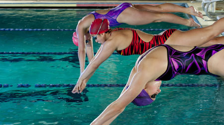Swimmers diving off starting blocks