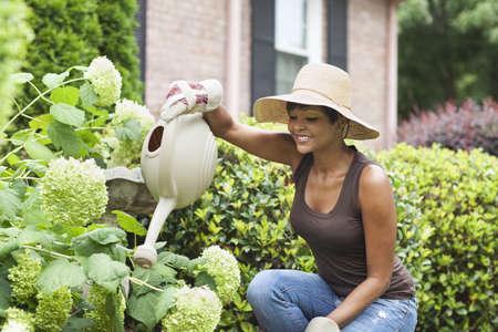 African American woman watering plants