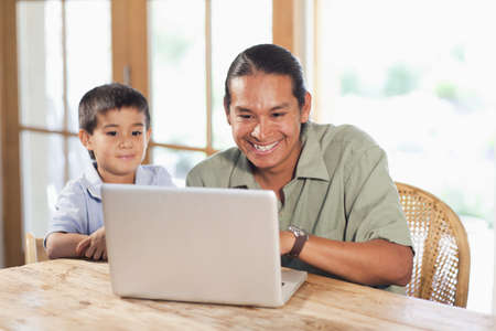 Father and son using laptop together LANG_EVOIMAGES