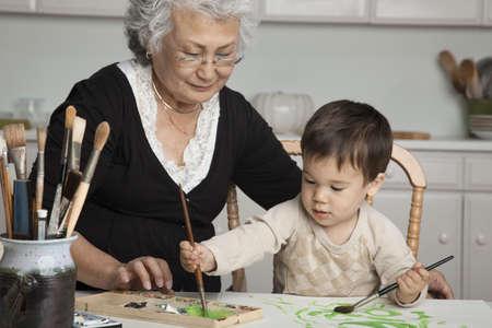 Grandmother watching grandson painting