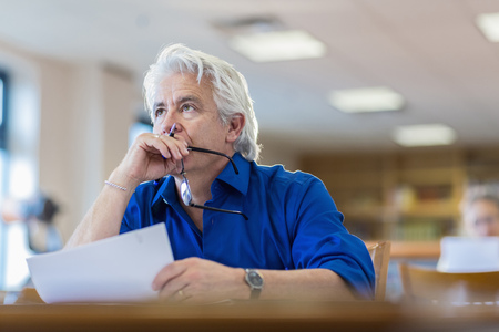 Man Reading Paperwork In Library LANG_EVOIMAGES