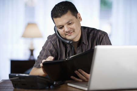 Mixed Race Man Using Laptop And Talking On Telephone