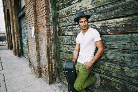 Mixed Race Musician Holding Guitar Case Near Industrial Building