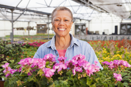 Mixed Race Woman Standing With Flowers In Plant Nursery LANG_EVOIMAGES