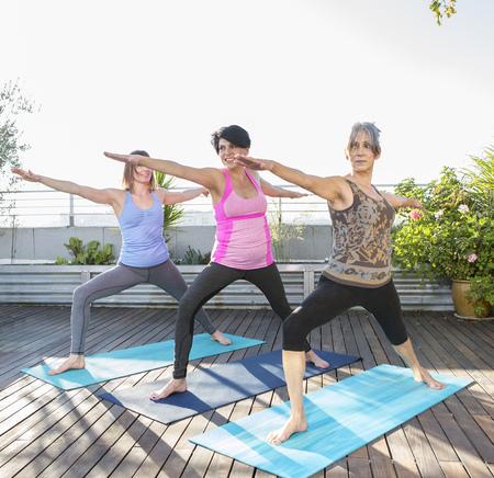 Women Practicing Yoga Together On Urban Rooftop LANG_EVOIMAGES