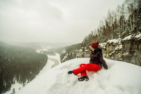 Caucasian Hiker Sitting On Snowy Hilltop
