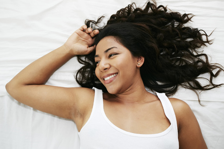 Hispanic Woman Laying On Bed LANG_EVOIMAGES