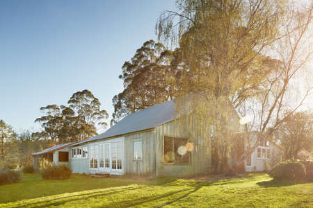 Sunlight Over Farmhouse And Green Lawn
