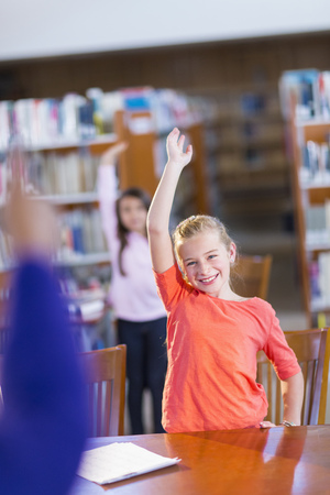 Student Raising Her Hand In Library LANG_EVOIMAGES