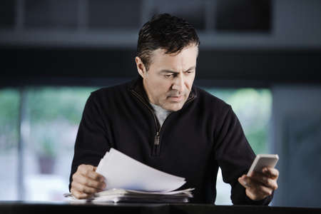 Hispanic Businessman Using Cell Phone And Looking At Paperwork LANG_EVOIMAGES