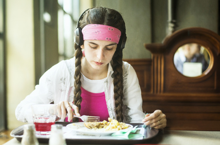 Caucasian Woman Wearing Headphones Eating In Dining Room