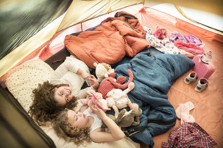 Girls Using Cell Phones In Camping Tent