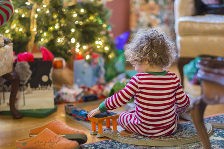 Caucasian Baby Boy Playing With Toys Near Christmas Tree LANG_EVOIMAGES