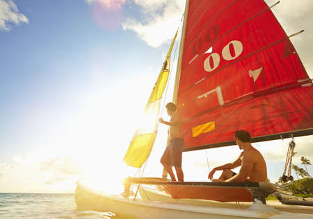 Caucasian Men On Sailboat In Ocean