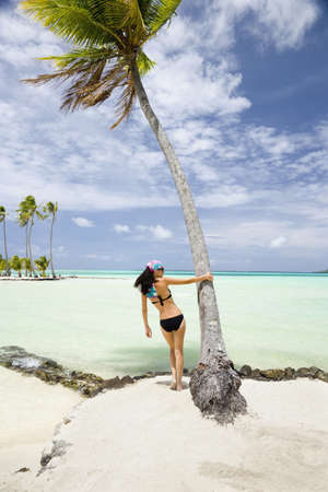 Pacific Islander Woman Standing Under Palm Tree On Tropical Beach