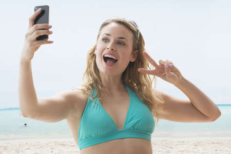 Caucasian Woman Taking Self Portrait On Beach