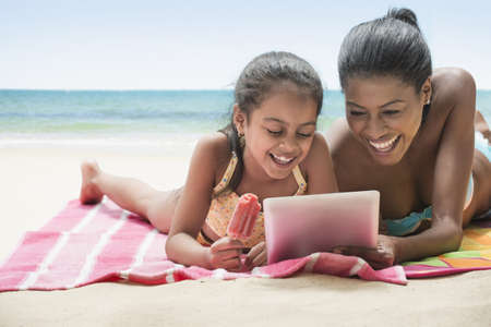 Hispanic Mother And Daughter Using Digital Tablet On Beach