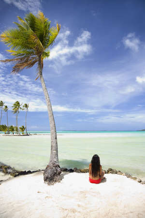Pacific Islander Woman Sitting On Tropical Beach LANG_EVOIMAGES