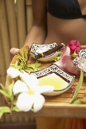 Close Up Of Pacific Islander Woman Carrying Tray Of Body Oils LANG_EVOIMAGES