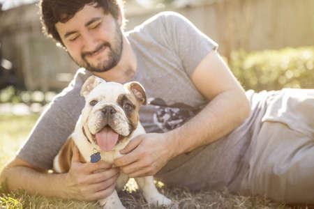 Caucasian Man Petting Dog On Lawn