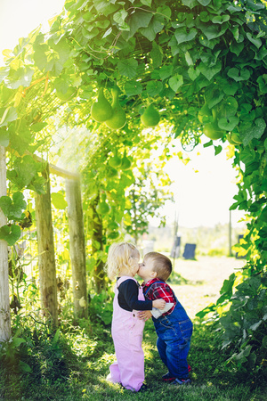 Caucasian Children Kissing Under Ivy Leaves LANG_EVOIMAGES
