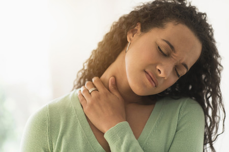 Close Up Of Mixed Race Woman Rubbing Sore Neck LANG_EVOIMAGES