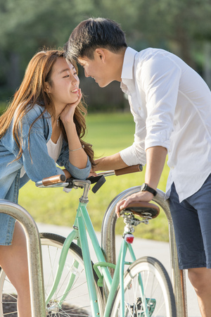 Korean Couple Locking Bicycle To Rack In Park