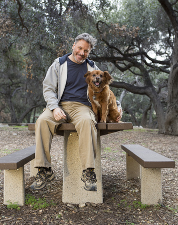 Caucasian Man And Dog Sitting On Picnic Table In Park